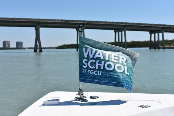 A Florida Gulf Coast University Water School Flag waves on a university research boat.