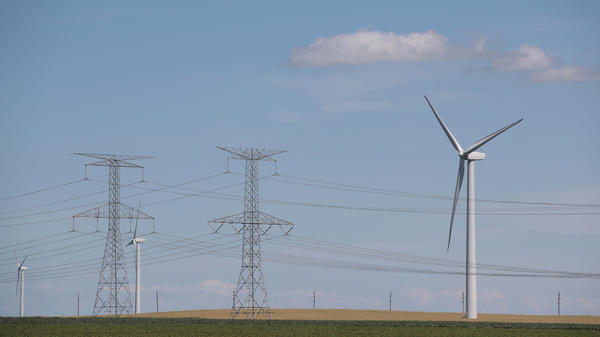 Power lines and power-generating windmills rise above the rural landscape on June 13, 2018, near Dwight, Ill. Driven by falling costs, global spending on renewable energy sources like wind and solar is now outpacing investment in electricity from fossil fuels and nuclear power.