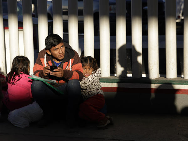 A migrant and his children wait to hear whether their number is called to apply for asylum in the United States, at the border in Tijuana, Mexico.