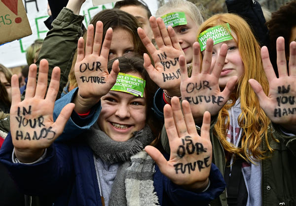 "In Berlin, youths show their hands bearing the inscriptions ""Our future in your hands"" during the protests."