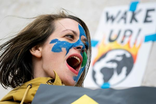 In Austria, a youth shouts slogans during a climate protest outside the Hofburg palace in Vienna.
