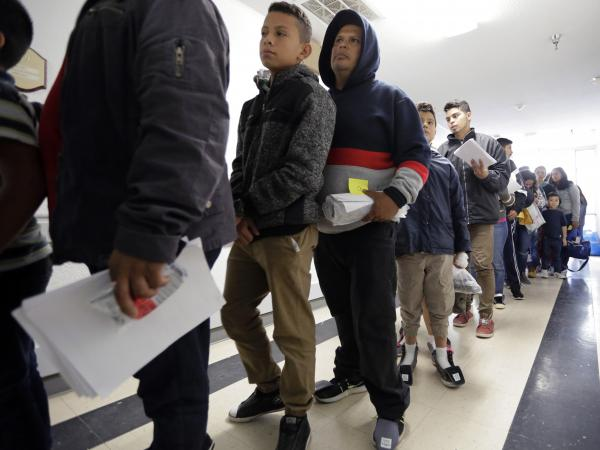 A line of migrants released by U.S. immigration authorities waits to check in at the Catholic Charities shelter in McAllen, Texas on Jan. 11.