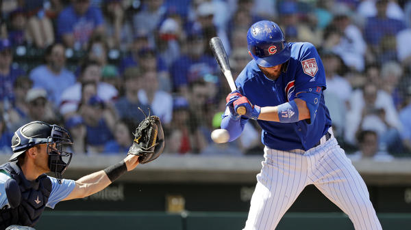 Chicago Cubs' Kris Bryant, right, is hit by a pitch as Seattle Mariners catcher Austin Nola looks on at a spring training baseball game on Tuesday.
