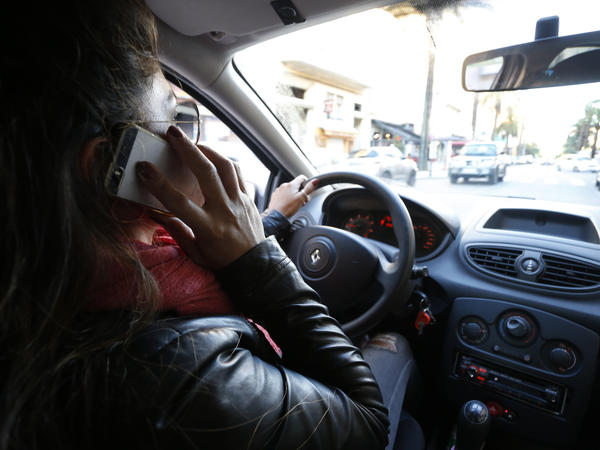 A woman speaks on her phone while driving. Both drivers and walkers use cell data 4,000 percent more than they did in 2008, which means they aren't watching the roads.
