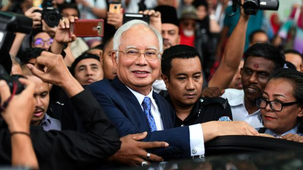 Najib Razak, Malaysia's former prime minister, leaves court in Kuala Lumpur on Wednesday — the first day in his trial over charges that he used a slush fund to put millions of dollars into his own accounts.