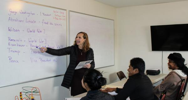 Birgit Lemke reviews with refugees questions that may appear on a U.S. citizenship test.