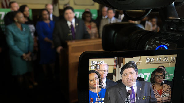 Gov. J.B. Pritzker, surrounded by Democratic lawmakers, spoke with reporters after the formal introduction of the constitutional amendment needed to advance his graduated income tax proposal.