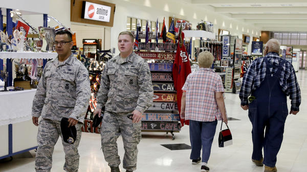 Service members and civilians walk through a store on Offutt Air Force Base in Nebraska in 2017. The Army and Air Force Exchange Service, which oversees military retail facilities, recommended this week that stores show sports instead of news on their common-area televisions.