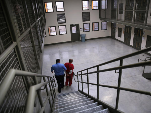 """A guard escorts a detained immigrant from his """"segregation cell"""" back into the general population at the Adelanto Detention Facility in November 2013. Today the privately run ICE facility in Adelanto, Calif., houses nearly 2,000 men and women and has come under sharp criticism by the California attorney general and other investigators for health and safety problems."""