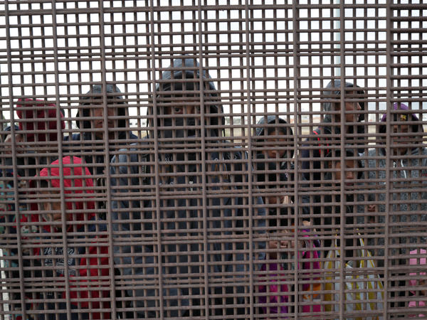 Central American migrants stand at the U.S.-Mexico border fence in El Paso, Texas. The migrants turned themselves in to U.S. Border Patrol agents, seeking political asylum in the United States.