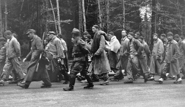 Nazi guards force Jewish prisoners on a death march during World War II. The fifth man from the right is Leo Wolf, who survived the Holocaust and co-founded the Holocaust Museum & Learning Center with Tom Green and Bill Kahn.