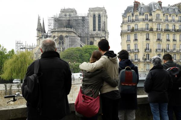 People hug while looking at Notre Dame Cathedral in the aftermath of a fire that devastated the cathedral.