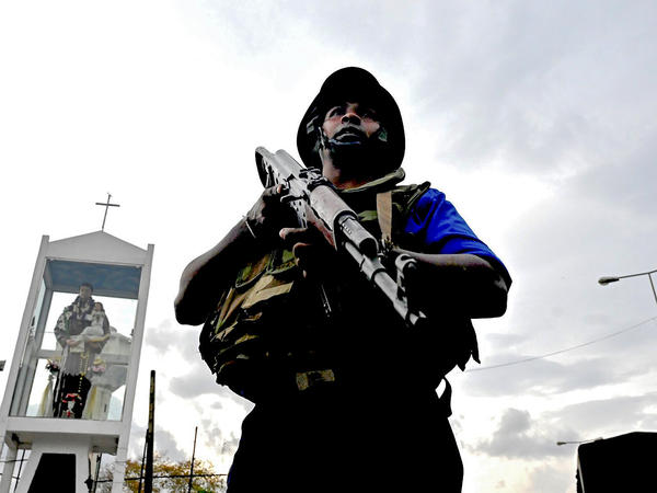 A Sri Lankan soldier stands guard near the site of a car explosion after police tried to defuse a bomb near St. Anthony's Shrine in Colombo on Monday, the day after a series of bomb blasts targeting churches and luxury hotels in Sri Lanka.