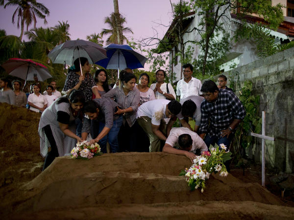 Relatives place flowers after the burial of three family members who died in an Easter Sunday bomb blast at St. Sebastian Church in Negombo, Sri Lanka, on Monday.