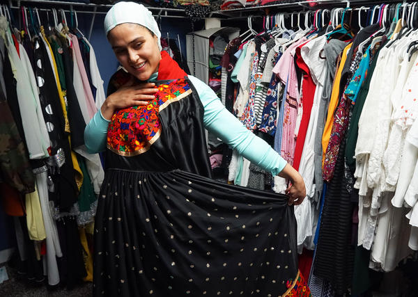 Mojda Sidiqi models one of her designs, a long black silk dress with an embroidered brocade bib.