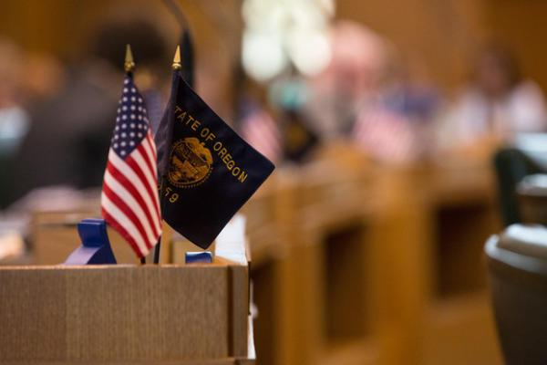 <p>The American and Oregon state flags adorn a desk on the House floor at the Capitol in Salem, Ore., Tuesday, April 2, 2019.</p>