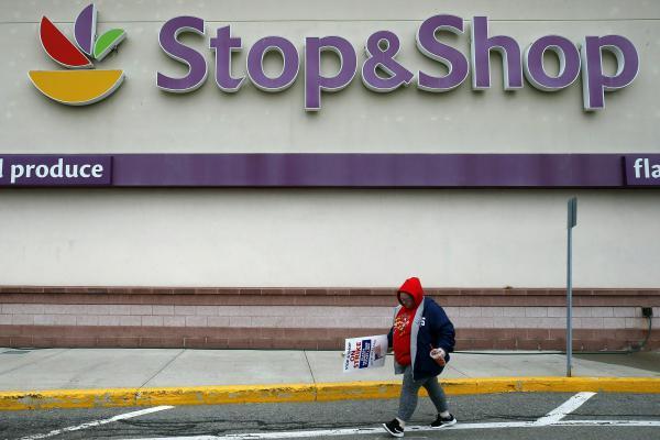 A striking worker walks outside a Stop & Shop supermarket in Revere, Mass., last week.