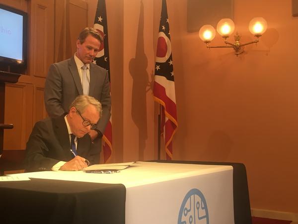 Gov. DeWine signs executive order as Lt. Gov. Jon Husted looks on