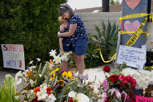 Mourners Heather Foy and her son Marshall, who live in the neighborhood, embrace at a makeshift memorial across the street from the Chabad of Poway Synagogue in Poway, California, one day after a teenage gunman opened fire, killing one person and injuring three others including the rabbi as worshipers marked the final day of Passover, authorities said. The shooting in the town of Poway, north of San Diego, came exactly six months after a white supremacist killed 11 people at Pittsburgh's Tree of Life synagogue.
