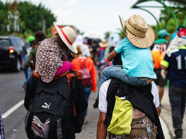 """Children are carried on the shoulders of Central American migrants heading to the U.S. along the road between Metapa and Tapachula, Mexico, on April 12. President Trump has called for measures to close what he calls the asylum """"loophole"""" amid a spike in border crossings."""