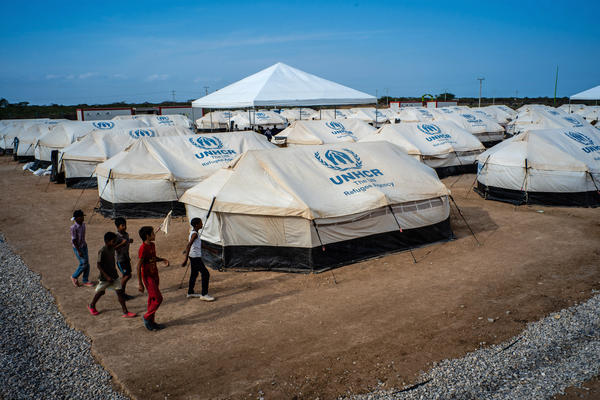 Venezuelan children walk past tents at the United Nations refugee agency camp in La Guajira, Colombia, in April. Local and national government agencies called on the UNHCR for aid after tens of thousands of Venezuelan migrants and refugees crossed the border into the Colombian town of Maicao.