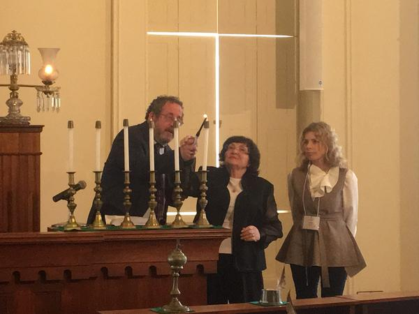 Khana Stolyar (center), an 82-year-old Holocaust survivor, lights the first candle during the annual Yom HaShoah Remembrance Service. She is joined by Rabbi Michael Datz and her granddaughter, Larisa Blyudaya.