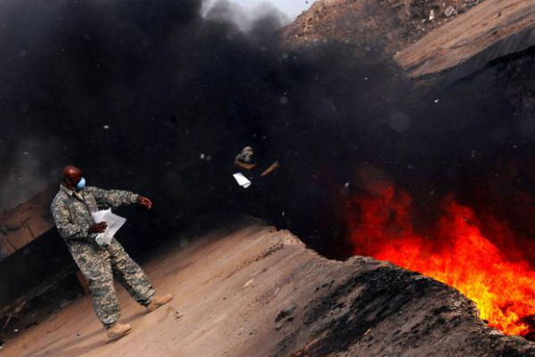 An Air Force master sergeant tosses unserviceable uniform items into a burn pit at Balad Air Base, Iraq, on March 10, 2008.