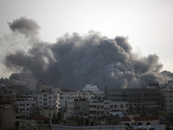 Black smoke caused by an Israeli airstrike billows over Gaza City, Sunday as Prime Minister Benjamin Netanyahu ordered the military to continue pounding the coastal city. Palestinian militants in the Gaza Strip also intensified a wave of rocket fire into southern Israel.