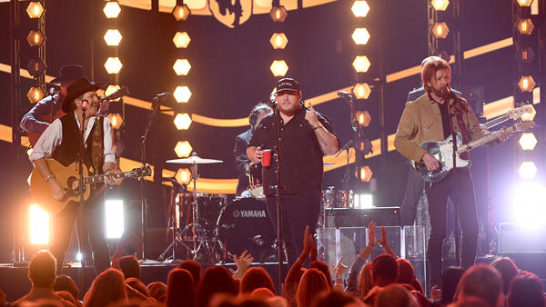 Kix Brooks (left) and Ronnie Dunn (right) of Brooks & Dunn perform with Luke Combs (center) during the Academy Of Country Music Awards in April. Combs appears on Brooks & Dunn's new album, <em>Reboot</em>, which features contemporary country stars collaborating with the duo on a dozen of its classic songs.