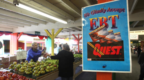 A sign announces the acceptance of electronic benefit transfer cards at a farmers market in California. Anti-poverty groups fear that many low-income people might be pushed off programs such as food stamps under a possible change to how the government measures poverty.