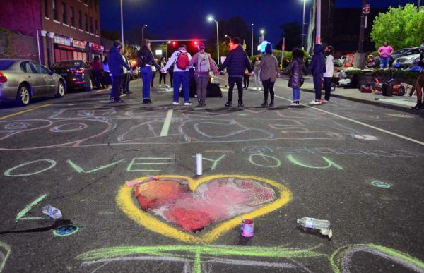 Activists and friends of Jayson Negron hold hands as they hold a vigil for him near the Walgreen's along Fairfield Ave in Bridgeport, Conn., on Thursday May 9, 2019.