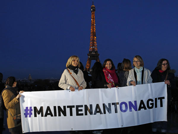 """French Culture Minister Françoise Nyssen (second right), Paris Mayor Anne Hidalgo (center) and women's rights activists hold a banner reading """"<em>Maintenant on agit</em>"""" (""""Now we act""""), on the eve of International Women's Day on March 7. They aim to raise funds to help women pursue justice, """"so that no woman ever again has to say #MeToo."""""""