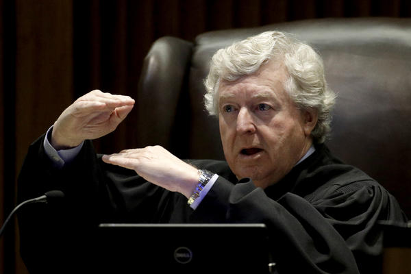 Kansas Supreme Court Justice Dan Biles asked how much would be enough for the state to demonstrate it has complied with a string of court orders to make school funding adequate.