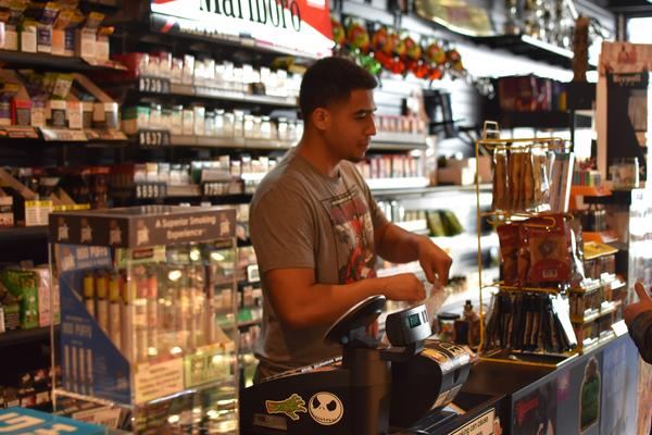 Logan Chase serves customers tobacco products and CBD at The Smoke Shop in DeKalb.