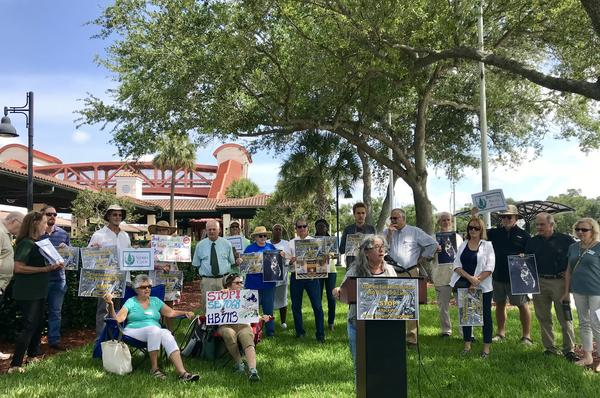 Diana Umpierre, center, asked Gov. Ron DeSantis to veto two transportation and housing bills Tuesday, in front of the Tri-Rail station in Hollywood.
