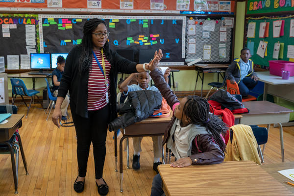 Brionna Taylor high-fives one of her second-graders at Bryan Hill Elementary School in St. Louis. Low pay is the reason most teachers quit, according to a new survey. Their students are the reason most said they stay.