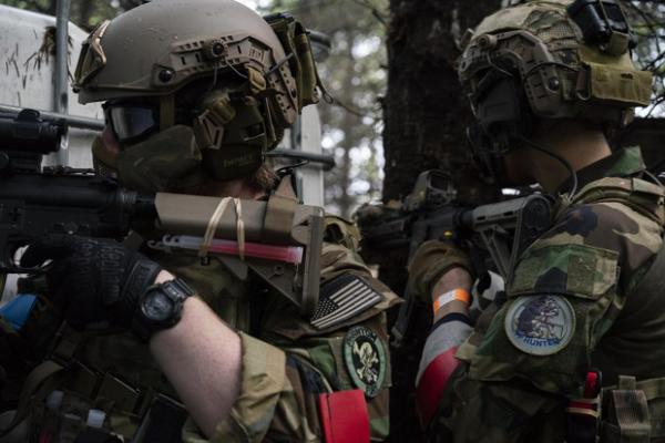 <p>Noah Wenger and Alex Bates look for opponents during an AirSoft game at Action Acres AirSoft on March 23, 2019, in Canby, Ore.</p>