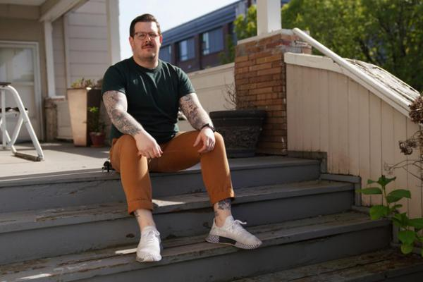 <p>Scott Luciano sits for a portrait on his front porch on May 4, 2019, in Portland, Ore.</p>
