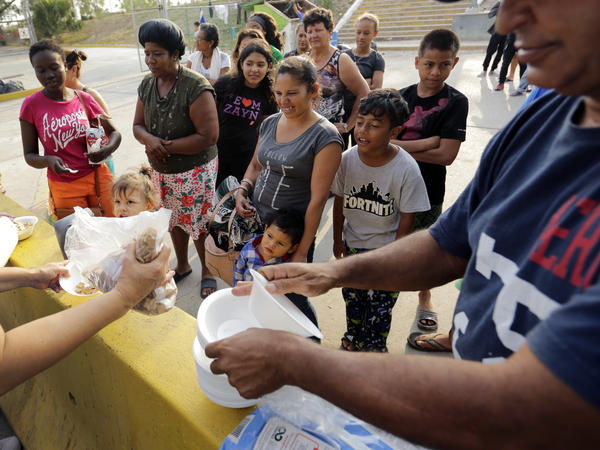 Migrants seeking asylum in the United States receive breakfast from a group of volunteers near the international bridge in Matamoros, Mexico.