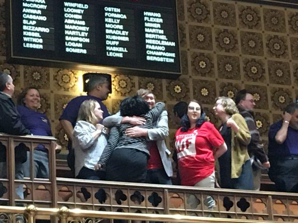 Supporters of the minimum wage celebrate in the Senate gallery after passage at nearly 3 a.m.
