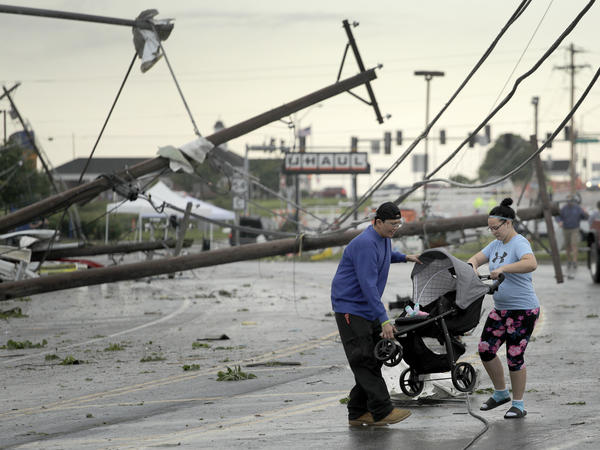 Jessica Rodgers and neighbor Ray Arellana carry a stroller carrying Rodgers' sister Sophia Rodgers over downed power lines as they head to Rodgers' mother's apartment to check on damage on Thursday after a tornado tore though Jefferson City, Mo., late Wednesday.
