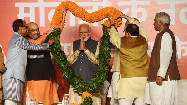 Indian Prime Minister Narendra Modi is adorned with a garland of flowers by members of his political party at their headquarters in New Delhi on Thursday, following a victory in the country's national elections.
