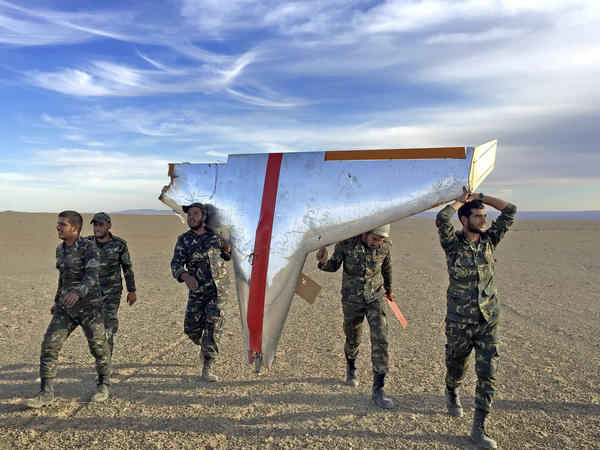 Iranian soldiers carry part of a target drone used in air-defense exercises. Iran is also turning some target drones into low-tech weapons for its proxies.