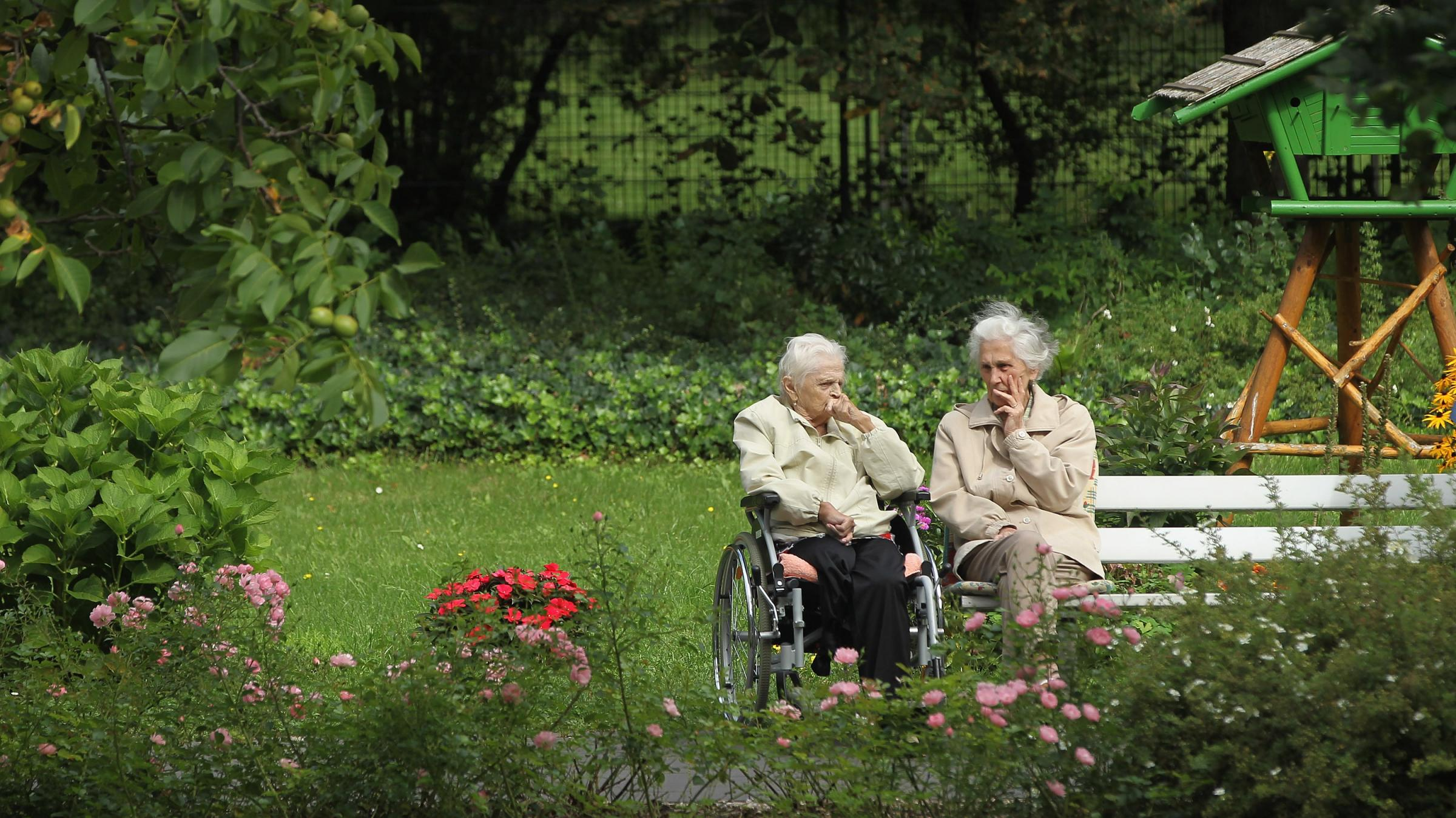 Two German Women Chat In The Gardens Of A Senior Care Home In Berlin