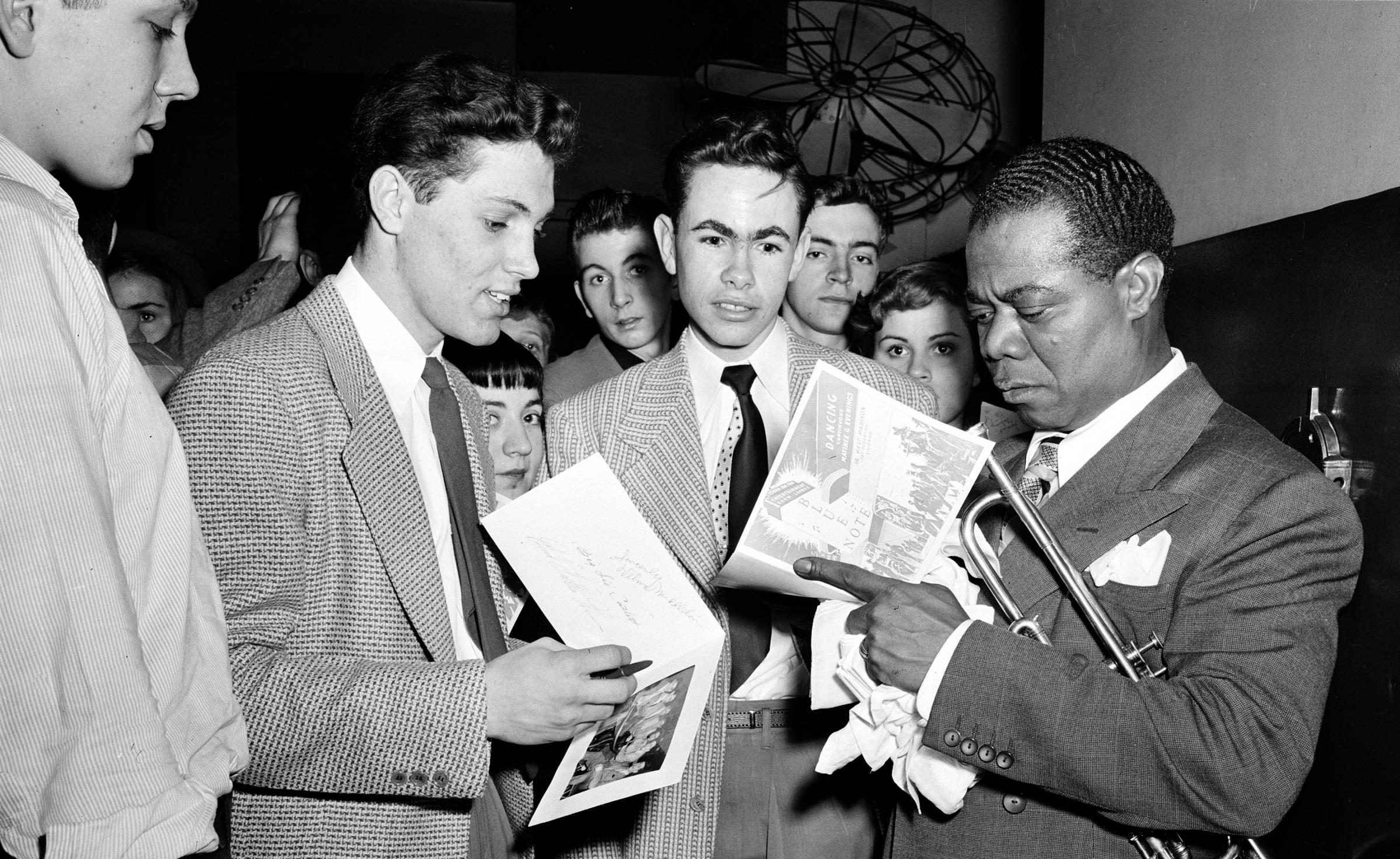 don t you dare call me a hipster i sir am a hep cat kut jazz trumpeter louis armstrong signs autographs in the blue note nightclub in chicago in 1948
