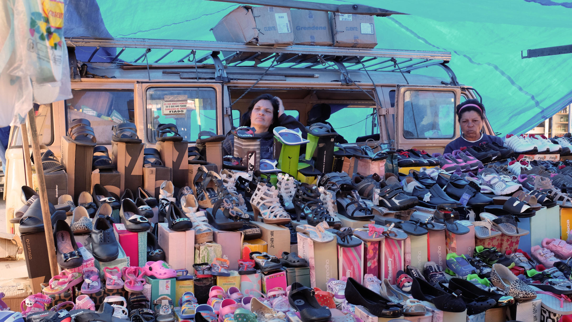 5dc0021d34ef3 A woman waits for customers at a street market where she sells shoes in Sao  Paulo. View Slideshow 1 of 2