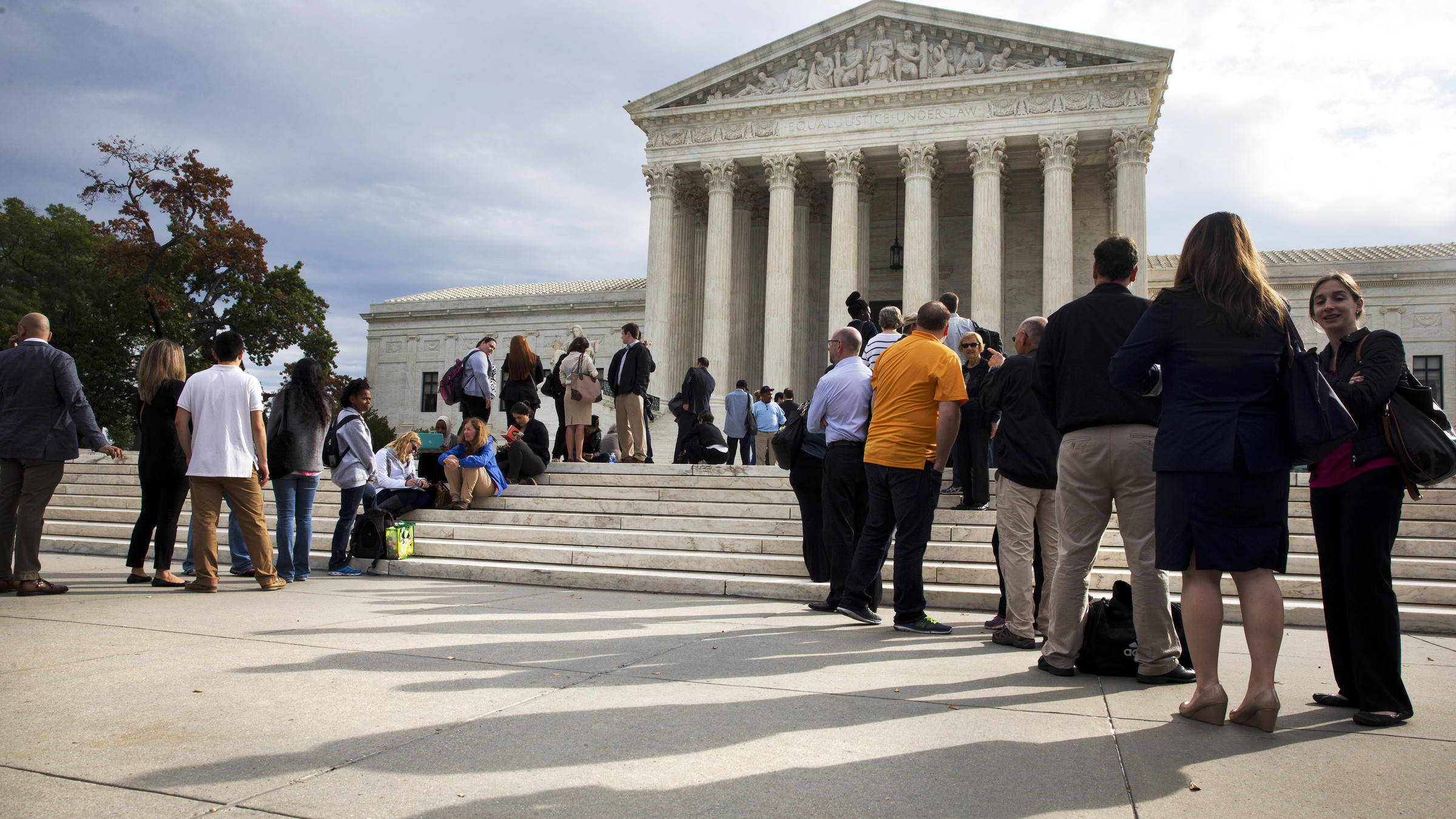 People line up outside the Supreme Court Tuesday ahead of arguments in ...