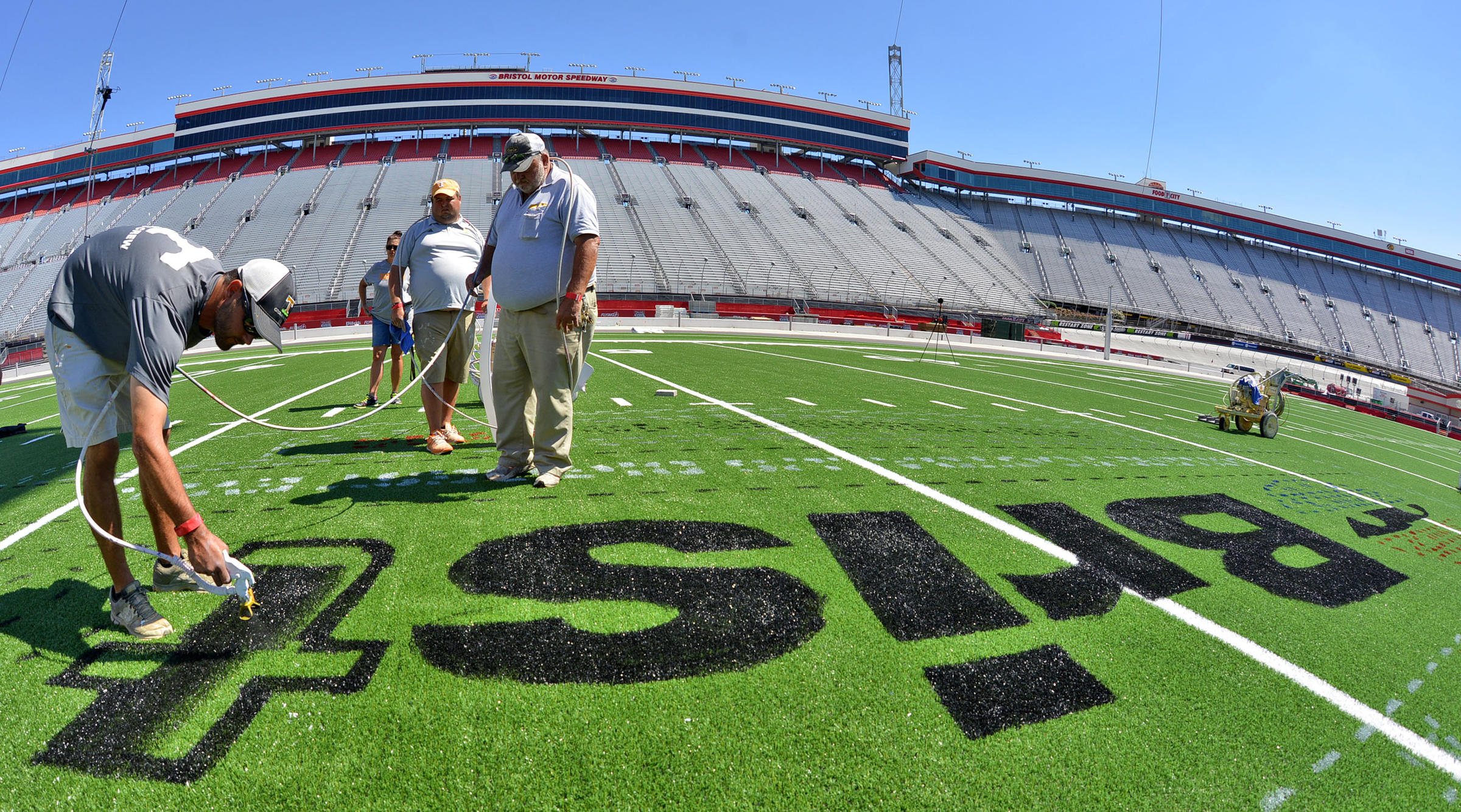 """Members of the University of Tennessee grounds crew paint the """"Battle at Bristol"""" logo on the football field at Bristol Motor Speedway in Bristol, Tenn."""