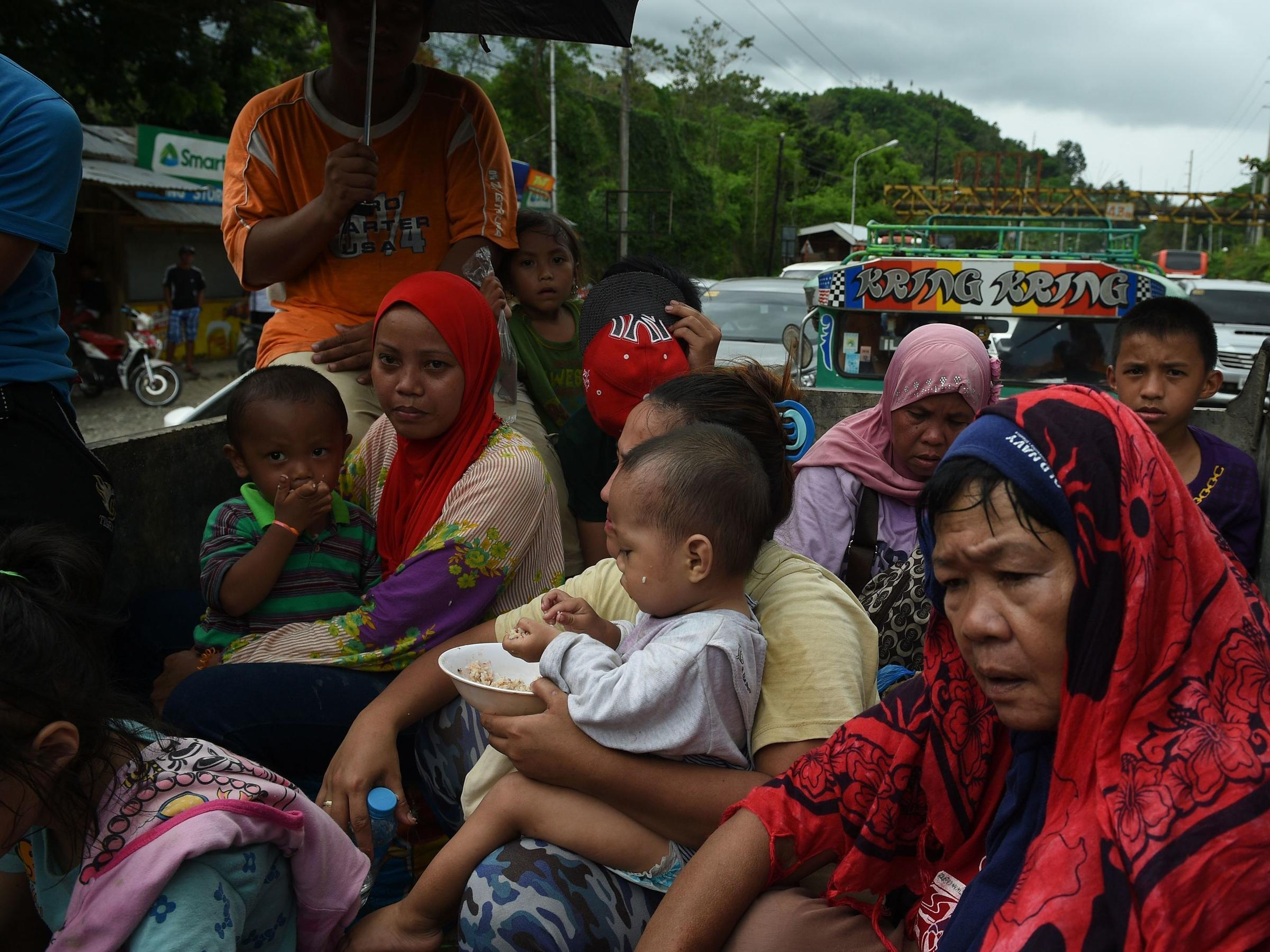 Residents fleeing Marawi City sit cramped in a truck that's stuck gridlock near a police checkpoint at Iligan City nearby on Mindanao