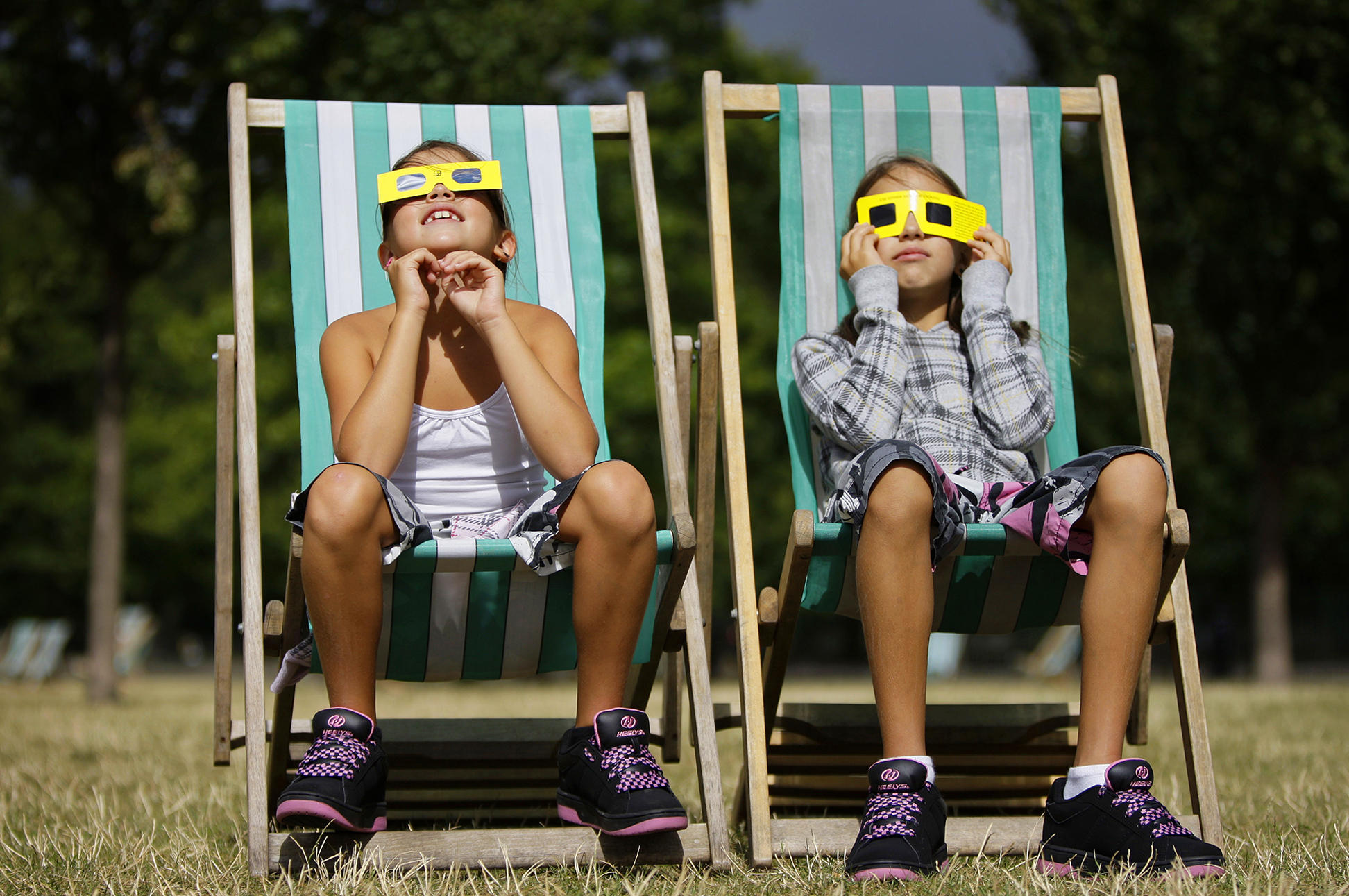 Neza Pintaric 9 and sister Ula 11 right from Slovenia watch the partial eclipse of the sun through solar glasses in Hyde Park in central London Friday
